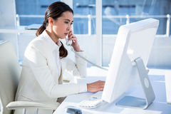 Smiling businesswoman using computer and telephone Royalty Free Stock Images