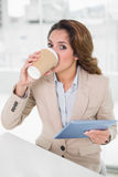 Smiling businesswoman using digital tablet at her desk drinking from disposable cup Stock Images