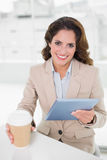 Smiling businesswoman using digital tablet at her desk holding disposable cup Stock Photos