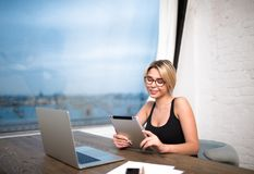 Smiling businesswoman using digital tablet and portable net-book. Female intelligent developer sites reading publication on touch pad, sitting at table with Stock Photography