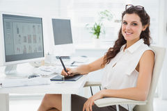 Smiling businesswoman using digitizer at desk Stock Photos