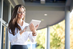 Smiling businesswoman using electronic tablet outside Royalty Free Stock Image
