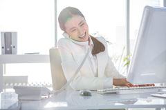Smiling businesswoman using her computer Stock Photo