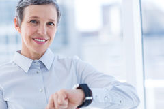 Smiling businesswoman using her smartwatch Stock Photo