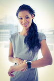 Smiling businesswoman using her smartwatch Royalty Free Stock Photography