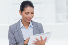 Smiling businesswoman using her tablet pc Stock Photo