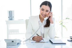Smiling businesswoman using her telephone Royalty Free Stock Images