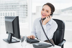 Smiling businesswoman using landline phone and computer in office Royalty Free Stock Photo