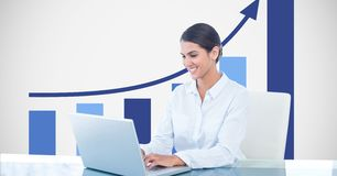 Smiling businesswoman using laptop against graph Royalty Free Stock Image