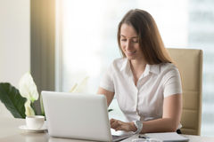 Smiling businesswoman using laptop, happy employee communicating. Smiling businesswoman using laptop computer in office, happy employee communicating online at Stock Image