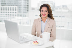 Smiling businesswoman using laptop at her desk and having coffee Royalty Free Stock Photos