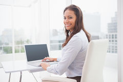 Smiling businesswoman using laptop at her desk Royalty Free Stock Photos