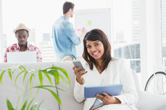 Smiling businesswoman using laptop and mobile on couch Royalty Free Stock Photo