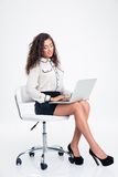 Smiling businesswoman using laptop on the office chair Stock Photography