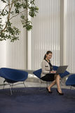 Smiling Businesswoman Using Laptop In Office Lobby Royalty Free Stock Images