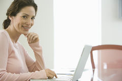 Smiling Businesswoman Using Laptop In Office Stock Photography