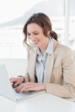 Smiling businesswoman using laptop in office Stock Image