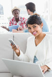 Smiling businesswoman using mobile and laptop on couch Royalty Free Stock Photos