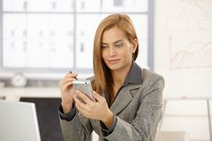 Smiling businesswoman using palmtop. In bright office Stock Photo