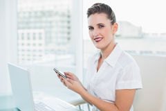 Smiling businesswoman using phone at home Royalty Free Stock Image