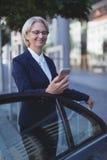 Smiling businesswoman using phone Stock Photo