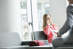 Smiling businesswoman using smart phone while sitting at lobby in convention center Royalty Free Stock Photos