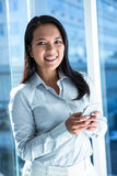 Smiling businesswoman using smartphone and looking at camera Stock Photo