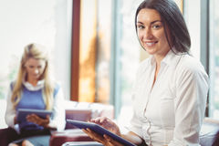 Smiling businesswoman using tablet with colleagues behind Royalty Free Stock Photo