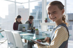 Smiling businesswoman using tablet while colleagues discussing in background Stock Photography