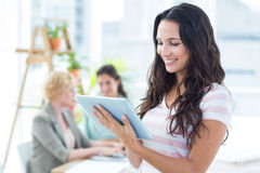 Smiling businesswoman using a tablet with colleagues Royalty Free Stock Photography