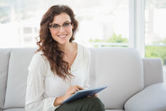 Smiling businesswoman using tablet on couch Royalty Free Stock Photo