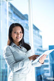 Smiling businesswoman using tablet and looking at camera Stock Photos