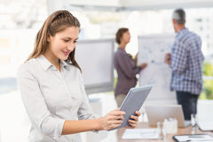 Smiling businesswoman using tablet in a meeting Royalty Free Stock Photos
