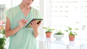 Smiling businesswoman using a tablet. In the office stock footage