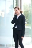 Smiling businesswoman walking outside with cell phone Stock Photo