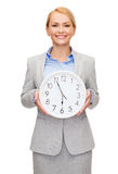 Smiling businesswoman with wall clock Royalty Free Stock Images