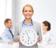 Smiling businesswoman with wall clock Stock Image