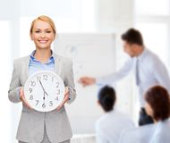 Smiling businesswoman with wall clock Stock Images