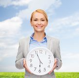Smiling businesswoman with wall clock Stock Photo