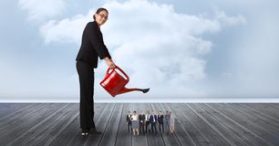 Smiling businesswoman watering employees on pier against cloudy sky Stock Image