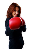 Smiling businesswoman wearing boxing gloves punching Royalty Free Stock Images