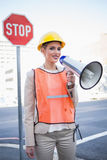 Smiling businesswoman wearing builders clothes shouting in megap Royalty Free Stock Images
