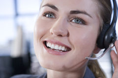 Smiling businesswoman wearing a call centre headset Royalty Free Stock Photos