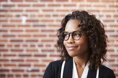 Smiling Businesswoman Wearing Glasses Standing Against Brick Wall In Modern Office stock photos