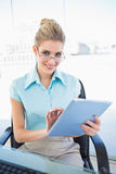 Smiling businesswoman wearing glasses using tablet Stock Photo
