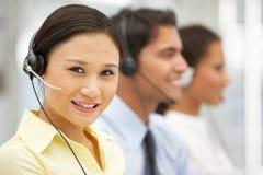 Smiling businesswoman wearing headset. Businesswomen wearing headset smiling to camera Royalty Free Stock Photo