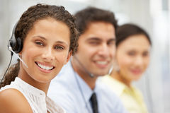 Smiling businesswoman wearing headset. Smiling businesswomen wearing headset looking to camera Royalty Free Stock Image