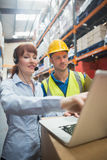 Smiling businesswoman wearing headset using laptop. In warehouse Stock Photography
