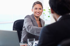 Smiling businesswoman welcomes customer Stock Images