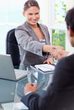 Smiling businesswoman welcomes customer in her office Royalty Free Stock Images